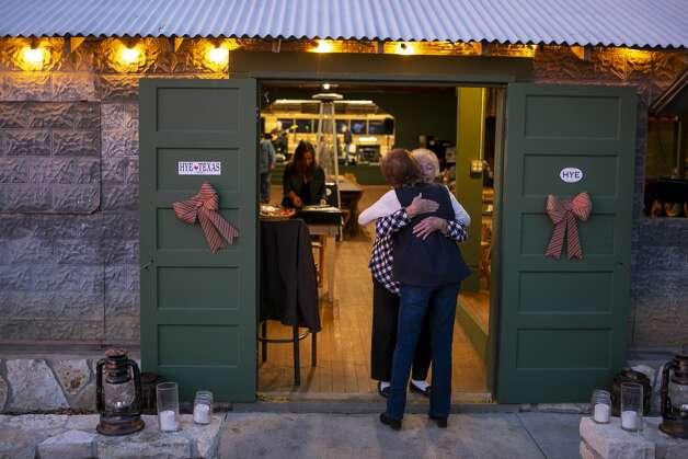 Ellen Felps of Hye greets a friend in the doorway of the recently reopened dance hall in Hye, Texas on Dec. 4, 2019. Photo: Josie Norris/Staff Photographer
