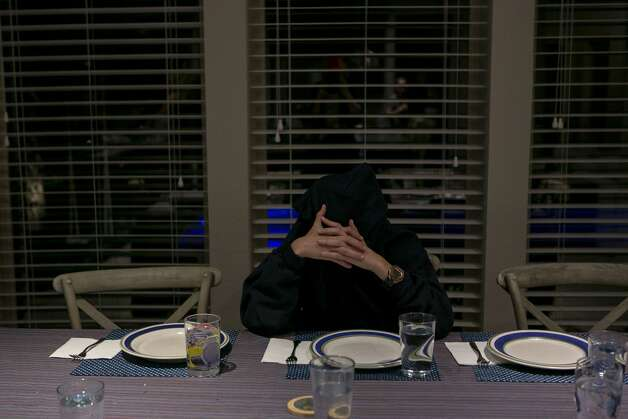 Luca Pelicano, 15, covers his face in his hoodie as he waits for his family to sit down for dinner in their home in New Braunfels, Texas on Nov. 18, 2019. Photo: Josie Norris/Staff Photographer