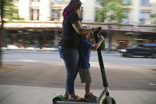A woman uses a scooter in tandem on the sidewalk along Houston Street in downtown San Antonio, Wednesday, March 13, 2019. The scooter rental comes with an agreement that limits the customer's ability to sue and accept other terms of the contract when they rent a scooter. Photo: Jerry Lara/Staff Photographer