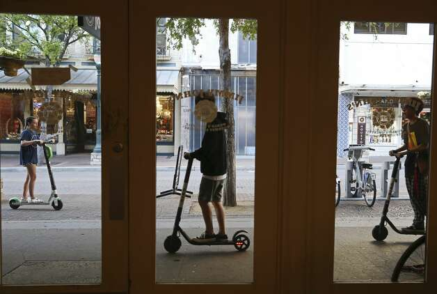Scooter riders use the sidewalk along Houston Street in downtown San Antonio, Wednesday, March 13, 2019. The scooter rental comes with an agreement that limits the customer's ability to sue and accept other terms of the contract when they rent a scooter. Photo: Jerry Lara/Staff Photographer