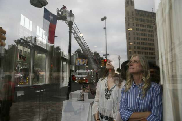 Michelle Deves left, and Maureen Deves, of Missouri, watch from their hotel window as a Texas flag is hung from fire trucks by Alamo Plaza for the funeral procession for San Antonio firefighter Greg Garza, Thursday, Oct. 24, 2019. Photo: Jerry Lara/Staff Photographer