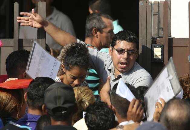An official attempts to restore order as migrants crowd the entrance to the Mexican Commission of Assistance to Refugees, (COMAR), in Tapachula, Chiapas, Monday, June 17, 2019. Hundreds gather at the commission daily in hopes of securing a humanitarian visa. Without the visa, migrants risk deportation back to their country. Photo: Jerry Lara/Staff Photographer