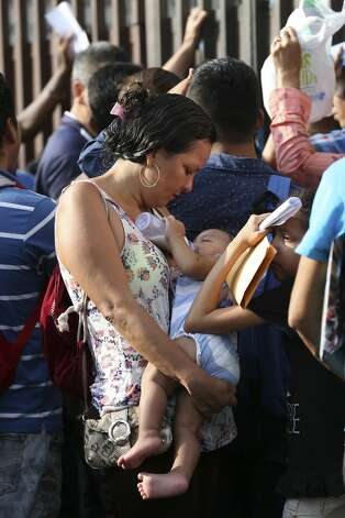 Honduran Medli Solis, 34, shields her 10-month-old daughter, Yarizne Monserrat, from the heat of the morning sun while waiting outside the Mexican Commission of Assistance to Refugee in Tapachula, Mexico, Monday, June 17, 2019. Solis, who has been in Mexico for over a month, is hoping for a humanitarian visa that would allow her to stay in the country without the fear of getting deported. Photo: Jerry Lara/Staff Photographer