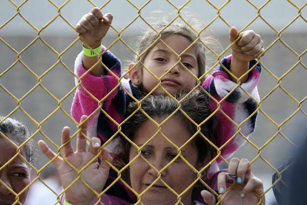 Six-year-old Daniela Fernanda Portillo Burgos, sits on the shoulders of her mother, Iris Jamilet, 39, as they look out through the fence of a immigrant shelter in Piedras Negras, Mexico, Tuesday, Feb. 5, 2019. The group numbering around 1,800 is at a state run shelter across the Rio Grande from Eagle Pass, Texas. The immigrants arrived on Monday and most are seeking asylum in the U.S. The family is from Honduras. Photo: Jerry Lara/Staff Photographer