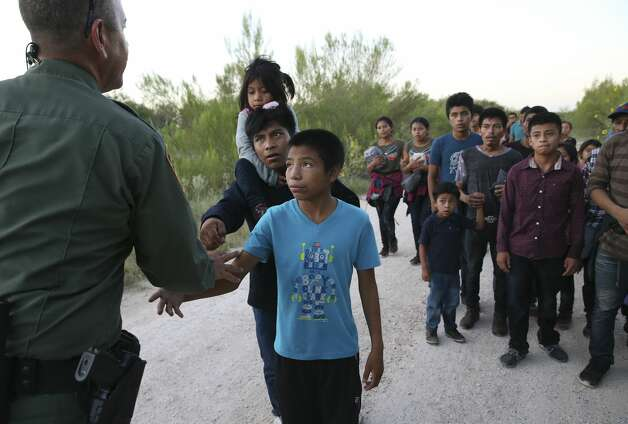Migrants reach out to shake hands with US Border Patrol Agent Carlos Ruiz as they turn themselves in after crossing the Rio Grande near the Anzalduas International Bridge in Hidalgo County, Texas, Thursday, July 18, 2019. The group consisted of mostly Central American migrants. Photo: Jerry Lara/Staff Photographer