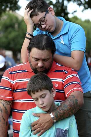 Michael Pules prays with his sons, Luke, 13, top, and Liam, 11, during a vigil at the University of Texas of the Permian Basin in Odessa, Texas on Sunday, Sept. 1, 2019. The vigil was for the victims of Saturday's mass shooting. Seth Aaron Ator, 36, of Odessa, is suspected of killing seven people an injuring 19 in a shooting spree on Saturday. Photo: Jerry Lara/Staff Photographer