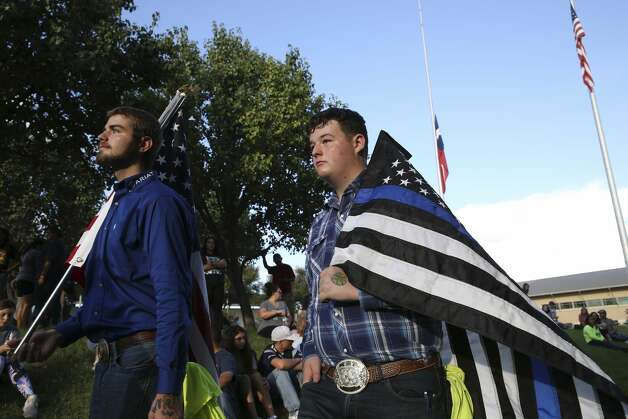 Holden Ewing, 16, left, carries a U.S. flag, while Travis Franklin 16, carries a law enforcement flag during a vigil at the University of Texas of the Permian Basin in Odessa, Texas on Sunday, Sept. 1, 2019. The vigil was for the victims of Saturday's mass shooting. Seth Aaron Ator, 36, of Odessa, is suspected of killing seven people an injuring 19 in a shooting spree on Saturday. Photo: Jerry Lara/Staff Photographer