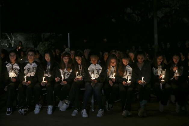 Members of the Clark High School cheerleaders hold candles during a vigil for the Olsen family at the Oblate Mission Lourdes Grotto, Wedneday, Jan. 16, 2019. The candlelight vigil was in memory of Nichol Olsen, 37, and her two daughters, Alexa Montez, 16, and London Sophia Bribiesca, 10, who were found dead at a home in Boerne last week. The Bexar County Medical has ruled the deaths murder-suicide committed by the mother. Bexar County Sheriff Javier Salazar has not closed the case and is still investigating. Montez was a member of the squad. Photo: Jerry Lara/Staff Photographer