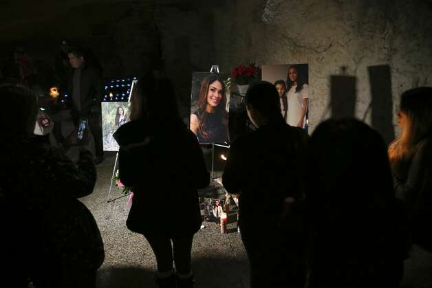 Friends and family gather in front of portraits of the Olsen family during a vigil at the Oblate Mission Lourdes Grotto, Wedneday, Jan. 16, 2019. The candlelight vigil was in memory of Nichol Olsen, 37, and her two daughters, Alexa Montez, 16, and London Sophia Bribiesca, 10, who were found dead at a home in Boerne last week. The Bexar County Medical has ruled the deaths murder-suicide committed by the mother. Bexar County Sheriff Javier Salazar has not closed the case and is still investigating. Photo: Jerry Lara/Staff Photographer