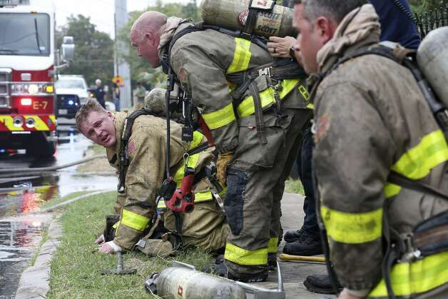 San Antonio Fire Department personnel have their oxygen tanks exchanged as they work a structure fire at the 500 block of West Drexel, Sunday, Oct. 20, 2019. According to Battalion Chief Tony Rodriguez, six fire unit responded to the house fire that destroy the front of the house. They were able to save the back of the residence. He estimated that the structure suffered around $40,000 in damages and since a source for the fire was not evident, arson investigators were call to the scene. Photo: Jerry Lara/Staff Photographer