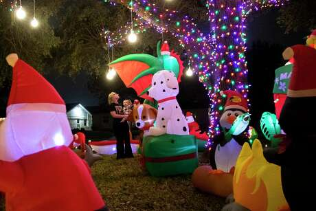Merry Harrison, 32, and Fox Harrison, 1, take a look at some of the 43 inflatable holiday figures the family has placed on the front yard of their home before heading to bed on Friday, Dec. 20, 2019, in Houston.