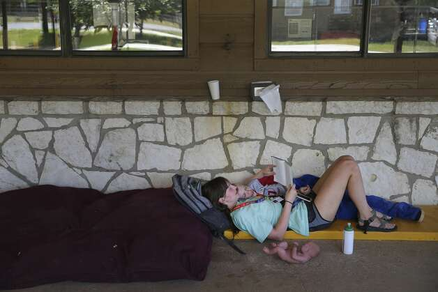 Camp counselor Kayla Smith spends a quiet moment reading a book with camper Jesse Pullin at CAMP Camp in Center Point, Texas on Thursday, Aug. 1, 2019. The camp offers children who are medically fragile or severely disabled a traditional summer camp experience and activities like swimming, canoeing, horseback riding and archery. Photo: Kin Man Hui/Staff Photographer