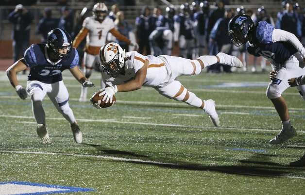 Madison's Darien Gill (02) dives in for a touchdown against Johnson's Kaleb Meza (33) and Djuan Hill (49) at their football game at Heroes Stadium on Friday, Nov. 8, 2019. Photo: Kin Man Hui/Staff Photographer