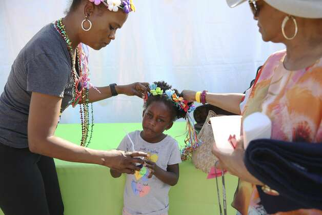 Lindsey Logan (left) puts a festive hair decoration on her four-year-old daughter, Braylee, as grandmother Gwen Logan helps out at The San Antonio African American Community Archive & Museum's Fiesta Family Blues Festival at the Wheatley Heights Sports Complex on Friday, Apr. 26, 2019. Photo: Kin Man Hui/Staff Photographer