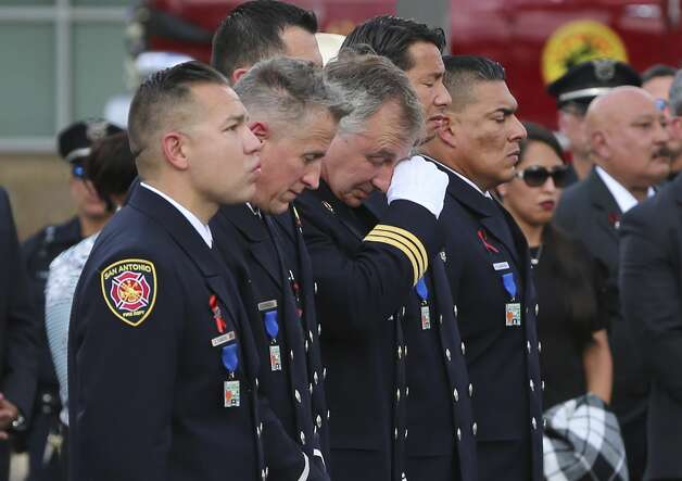 Firefighters who were friends of Greg Garza express emotion as the final alarm call for the fallen firefighter is toned out during his funeral service at Community Bible Church on Thursday, Oct. 24, 2019. Photo: Kin Man Hui/Staff Photographer