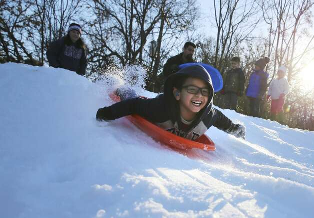 Kindergartener Josh Esquivel beams as he slides down a hill as the Sunshine Cottage School for Deaf Children holds a snow day for its students on Thursday, Jan. 24, 2019. Six hundred bags of ice were converted into more than 12,000 pounds of snow from Pure Party Ice Company. Photo: Kin Man Hui/San Antonio Express-News