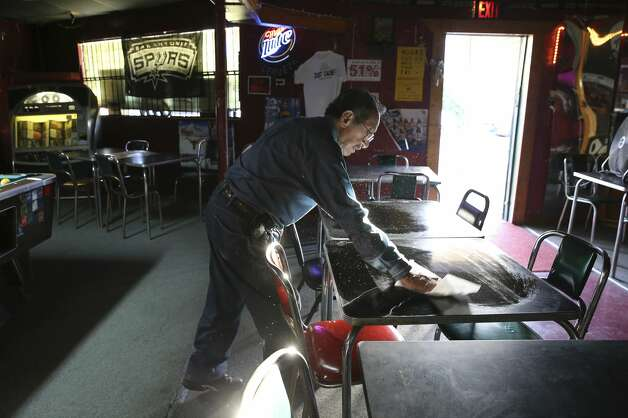 Tony Lopez of Tony's Bar on Brooklyn Avenue seen wiping down tables in anticipation of patrons will shutter his business after 20 years of serving cold brews and happy memories for patrons this Friday. Tony's is nestled in historical Irish Flats neighborhood in downtown with it's replica of the Tower of the Americas. Photo: Kin Man Hui/Staff Photographer