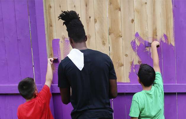 Spurs' Lonnie Walker, IV (second from left) assists nine-year-old Mario Barrera (left) to paint sections of fencing as Spurs players and staff pay a visit to SA Youth to help them paint and refurbish the playscape and fence line on the nonprofitÕs 1215 W. Poplar Street campus to help promote a healthy and active lifestyle on Thursday, May 30, 2019. Photo: Kin Man Hui/Staff Photographer