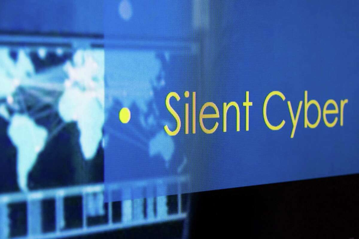 """A slide that reads """"Silent Cyber"""" is projected on a screen during a meeting at the AIR Worldwide Corp. headquarters in Boston, Massachusetts, U.S., on Friday, Sept. 6, 2019. The cost to businesses and insurers of a single global ransomware attack could hit $193 billion, with 86% of that uninsured, according to a 2019 report from a group that includes Lloyd's of London. Photographer: Adam Glanzman/Bloomberg"""