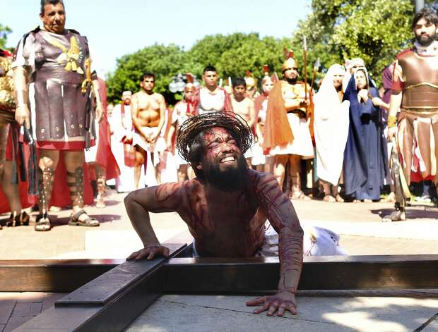Jesus, played by actor Charles Ramirez, falls for the first time while carrying the cross during the annual San Fernando Cathedral passion of Christ reenactment on Good Friday, April 19, 2019. The play depicts the final hours of the life of Jesus Christ on the day that he was crucified almost 2,000 years ago. Photo: Billy Calzada/Staff Photographer