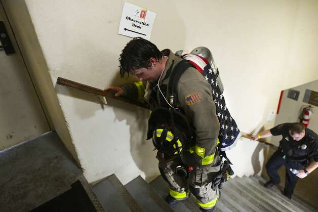 San Antonio firefighter Kiel Galvin climbs the last three steps to complete his climb as he carries a flag that he said has been through tours in Iraq during the San Antonio 110 9/11 Memorial Climb at the Tower of the Americas in Hemisfair Park on Wednesday, Sept. 11, 2019. Photo: Billy Calzada/Staff Photographer