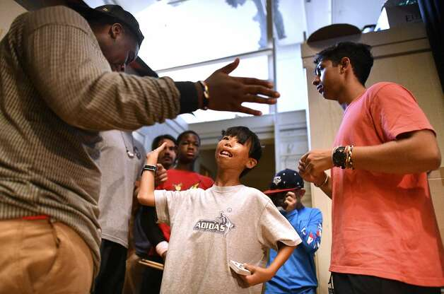 Connor Anderson, 11, middle, high-fives Marcus Brown, 16, backstage as they prepare to participate in a talent show at Texas Lions Camp in Kerrville on Friday, July 12, 2019. About fifty children are participating in the Texas Burn Survivor Society's weeklong, annual pediatric burn camp, called Camp David. Connor performed card tricks while Marcus danced. Photo: Billy Calzada/Staff Photographer