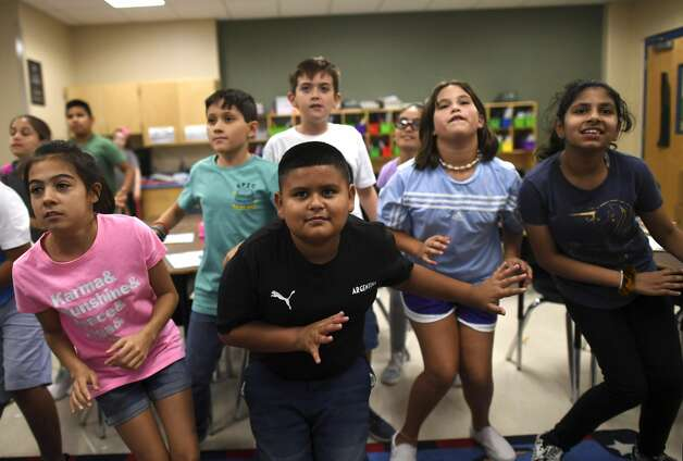 Luis Fabela, middle, dances with classmates in his fifth grade classroom at Ellison Elementary School. Photo: Billy Calzada/Staff Photographer