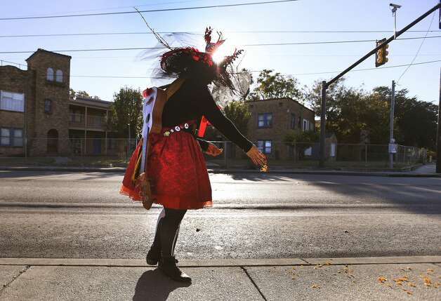 Keli Rosa Cabunoc Romero drops marigold petals during a D'a De Los Muertos on the Old Spanish Trail event along Fredericksburg Road on Saturday, Nov. 2, 2019. A procession traveled from the Deco District H-E-B at Fredericksburg Road and Hildebrand to the Centro Cultural Aztlan. Photo: Billy Calzada/Staff Photographer