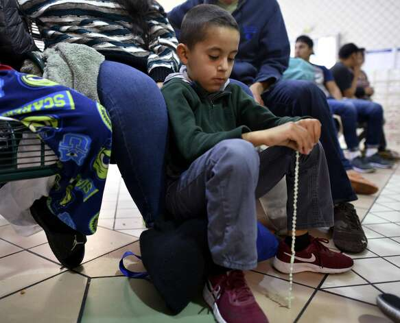 Justin, 7, a migrant from Honduras, sits with his family, waiting at the bus station in Laredo to board a bus on Friday, March 15, 2019. They were among a group of Central American migrants that were released after being apprehended and processed. Photo: Billy Calzada/Staff Photographer