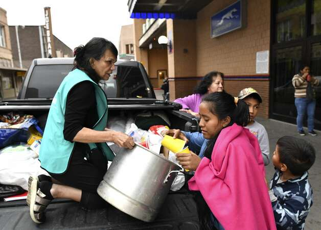 Elena Arredondo, a volunteer with Catholic Charities Laredo, offers chicken soup to Honduran migrants outside of the bus station in Laredo on Friday, March 15, 2019. Photo: Billy Calzada/Staff Photographer