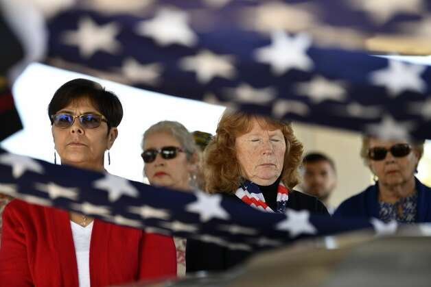 People listen during a service for two Marine Corps veterans, Gil Vargas, 65, who served from 1972-1976, and Alberto Vasquez, 67, who served for two months in 1973, and Army veteran John J. Flynn, 61, who served from 1977-1983, during their burial service at Fort Sam Houston on Wednesday, Feb. 27, 2019. The veterans left no known relatives, but over 100 people, including many from veterans groups, attended the service, which was arranged by the Bexar County Unaccompanied Veteran Burial Program and M.E. Rodriguez Funeral Home in San Antonio. Photo: Billy Calzada/Staff Photographer