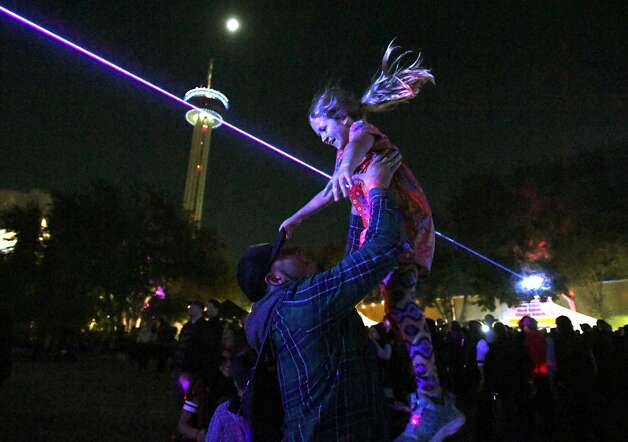 Olivia Barajas is tossed into the air during a laser light show by Hector Celestino de la Cruz during the Luminaria Contemporary Arts Festival at Hemisfair on Saturday night, Nov. 9, 2019. Photo: Billy Calzada/Staff Photographer