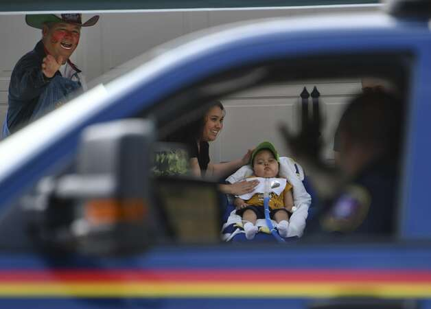 A Schertz EMS supervisor waves at Sabrina Hernandez and her son, Nathaniel ÒNathanÓ Hernandez, 6, who has been battling brain cancer since he was six months old, during a parade of fire engines, police vehicles and other equipment along the street where Nathan lives on Saturday, June 22, 2019. Photo: Billy Calzada/Staff Photographer