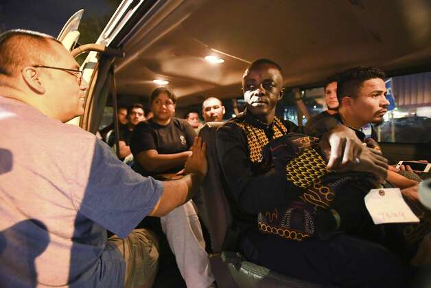 Immigrants from Cameroon, Nicaragua, Honduras and Venezuela are ministered to by Franciscan Father Andy Martinez as they arrive in San Antonio after their release from the South Texas Detention Complex in Pearsall on Thursday night, Nov. 22, 2019. Photo: Billy Calzada/Staff Photographer