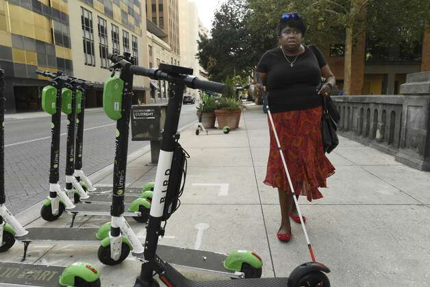 Athalie Malone, who is blind, is chair of the city's disability access advisory committee. She encounters scooters on a sidewalk along Market Street on the way to a city government meeting on Thursday, June 27, 2019. She said that she has tripped over scooters twice. Photo: Billy Calzada/Staff Photographer