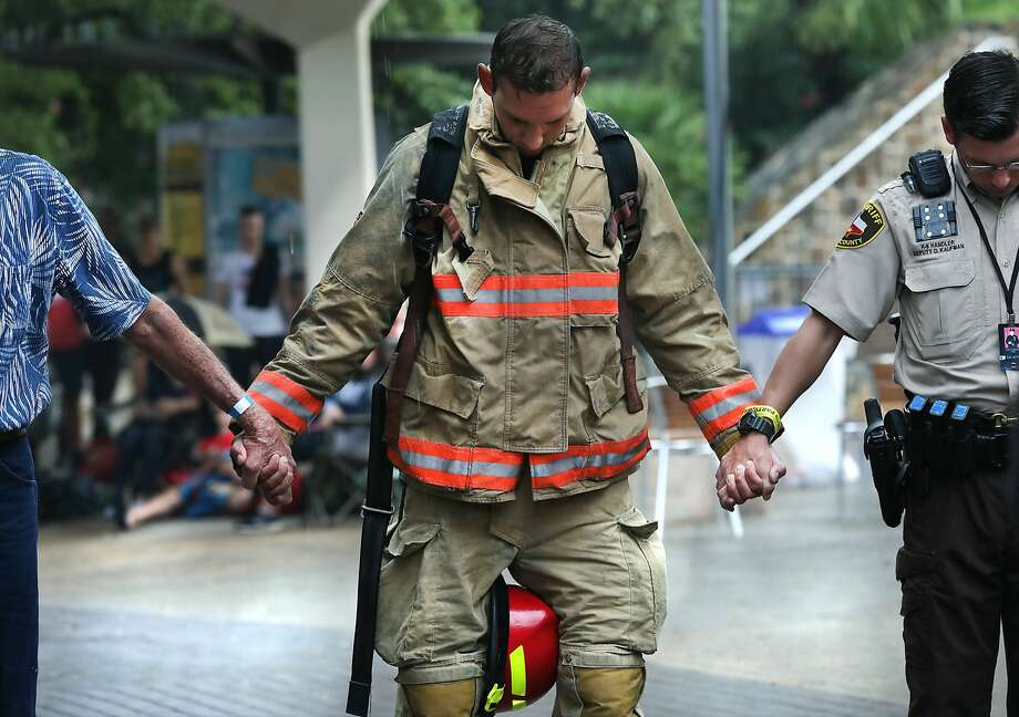 A firefighter holds hands with others during a prayer before the Memorial Tower Climb at the Tower of Americas in commemoration of Sept. 11, 2001. Photo: Bob Owen/Staff Photographer