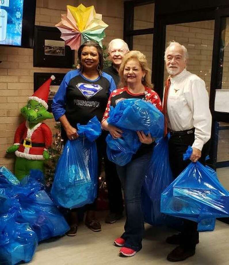 Members of the Rotary Club of Katy on Dec. 16 delivered some 140 bags filled with hundreds of toys for students at Hutsell, Sundown and Rhoads Elementary schools. Pictured at Hutsell Elementary are, from left: Principal Margie Blount, school counselor Magdalena Benavides and Rotarians Ken Burton and David Frishman. Photo: Courtesy Rotary Club Of Katy / Courtesy Rotary Club Of Katy