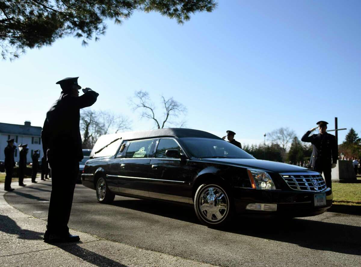 Officers salute as Greenwich Police Officer Justin Quagliani's hearse passes by during his funeral service at St. Michael the Archangel Church in Greenwich, Conn. Monday, Dec. 23, 2019. Officer Quagliani, a native of West Haven, died of a heart attack at age 38 on Dec. 17.