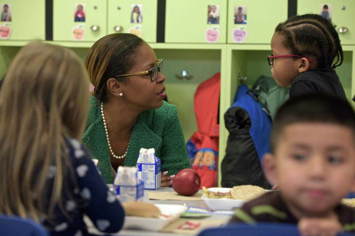 Nicole Taxiltaridis, the new director of early learning programs at the Connecticut Institute For Communities, talks with students enjoying lunch at Head Start in Danbury on Dec. 19.