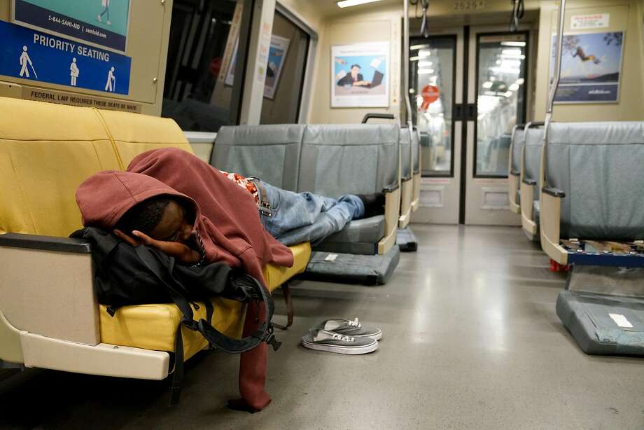 DeShawn Evans, 24, lies down on the last BART train bound for San Francisco International Airport at 1:29 a.m. in June. Photo: Guy Wathen / The Chronicle
