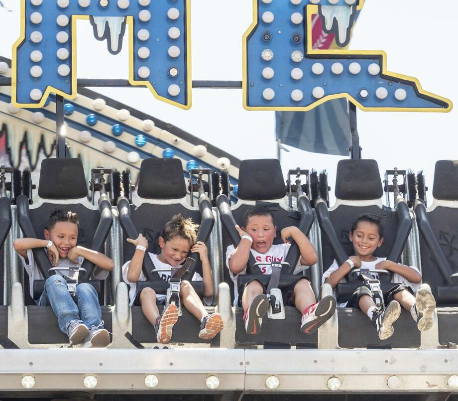 Youth take a ride on Aug. 24 at the Midland County Fair at the Horseshoe. Photo: Tim Fischer/Midland Reporter-Telegram