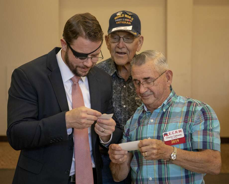 U.S. Rep. Dan Crenshaw looks at old World War II photos with veteran Jerry Wilkinson and his friend, Charles Calloway, May 30 at Odessa Country Club. Photo: Jacy Lewis/Reporter-Telegram