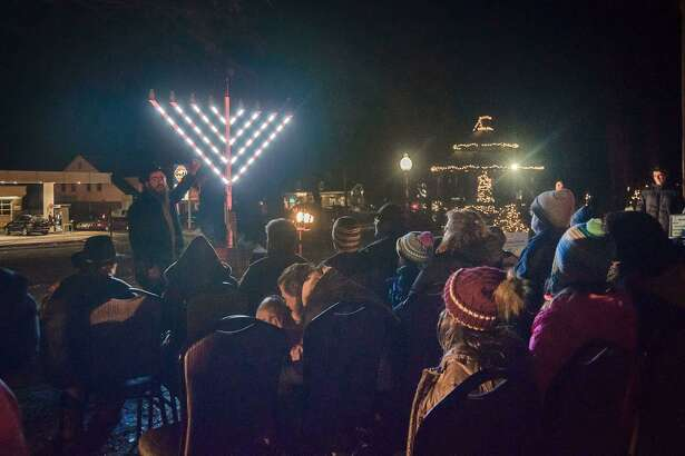 Rabbi Shneur Brook of Chabad of Shelton & Monroe speaks to those gathered at the annual menorah lighting celebration on the Huntington Green on Sunday, Dec. 22.