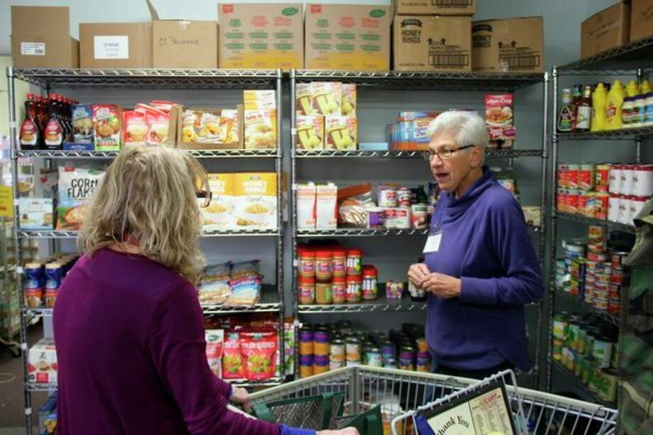 Teresa Calkins helps a client pick out food items at the Caseville Food Pantry. The pantry provides for the needy of Caseville, Caseville Township, and Lake Township. (Robert Creenan/Huron Daily Tribune)