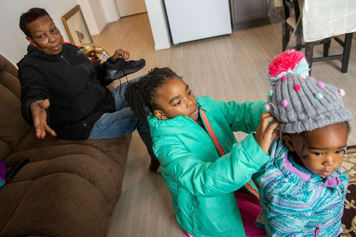 From left: Leola Brown, 69, with her grandchildren Ziani Brown, 8, and Lenia Brown, 2, get ready for their day at their home at BRIDGE Housing on Thursday, Dec. 19, 2019, in San Francisco, Calif. Leola lived across the street at 26th and Wisconsin streets for more than four decades before moving into BRIDGE Housing. The block of her former home is being demolished and developed with hundreds of apartments, as part of the Potrero HOPE SF project.