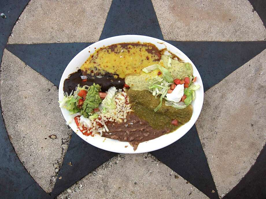 An enchilada sampler includes one enchilada ranchera, one enchilada creamy poblano, one enchilada verde, one enchilada poblana with mole and one Tex-Mex enchilada served with refried beans and guacamole at La Hacienda Scenic Loop. Photo: Mike Sutter /Staff