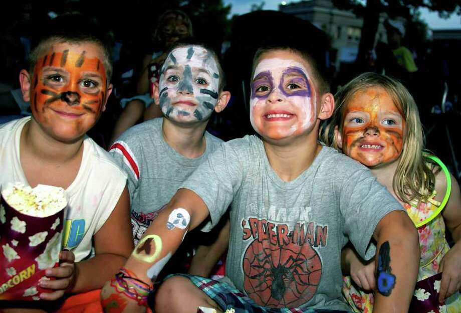 """SPECTRUM/Showing off faces decorated by artists fromthe Village Center for the Arts at the July 15, 2010 """"Movie Night on The Green"""" in New Milford are, from left to right, Ian, Jake and Kyle Lee, along with Sarah Falder, all from New Milford. The movie featured was """"Percy Jackson and the Olympians."""" The event was hosted by the New Milford Recreation Association as a a fundraiser for the New Milford High School Booster Club's Booster barn restroom project. Photo: Trish Haldin / The News-Times Freelance"""