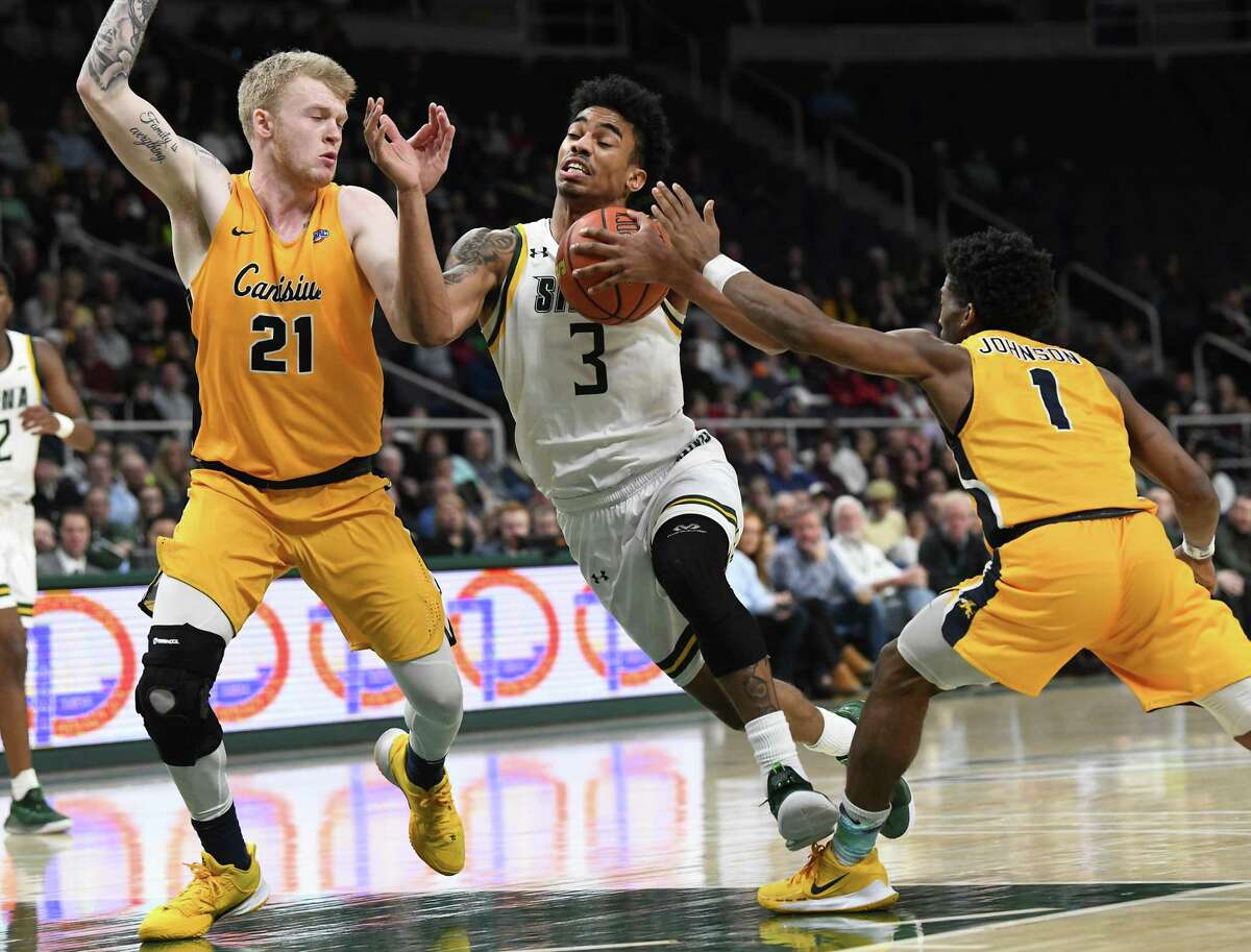Siena's Manny Camper drives to the hoop against Scott Hitchon, left, and Malik Johnson of Canisius during a basketball game on Monday, Dec. 23, 2019 in Albany, N.Y. (Lori Van Buren/Times Union)