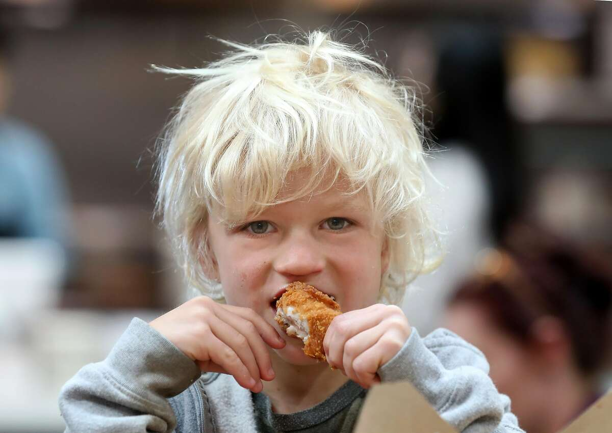 Wilds Moffett, 5 years old, visiting from Oceanside eats chicken from Minnie Bell's Soul Movement at the Public Market on Monday, Dec. 23, 2019, in Emeryville, Calif.