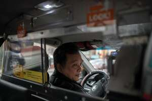Richard Chow at the wheel of his taxi in New York on Dec. 6, 2019. An economic crisis has swept over New York City's taxi industry, spreading financial ruin and personal despair, especially for owners of medallions, the permits that let people operate cabs.  (Kholood Eid/The New York Times)